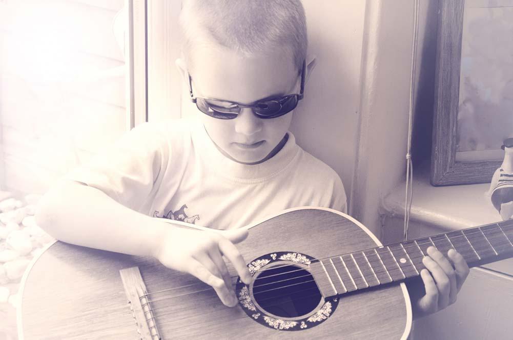 Jongen speelt gitaar stoer muziekschool